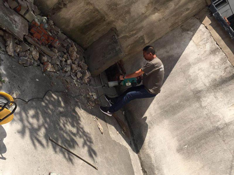 地面钻孔拆除装修:确保施工现场水通、电通。在切割过程中冷水具有对切割设备本身进行降温及避免扬尘的作用。根据现场情况,需对将要切除的混凝土实体进行设计排版,将实体分层、分块切除。流程是:施工准备——放线(弹线)——切割设备就位(固定)——混凝土(钢筋)切割——切块吊装——清理现场