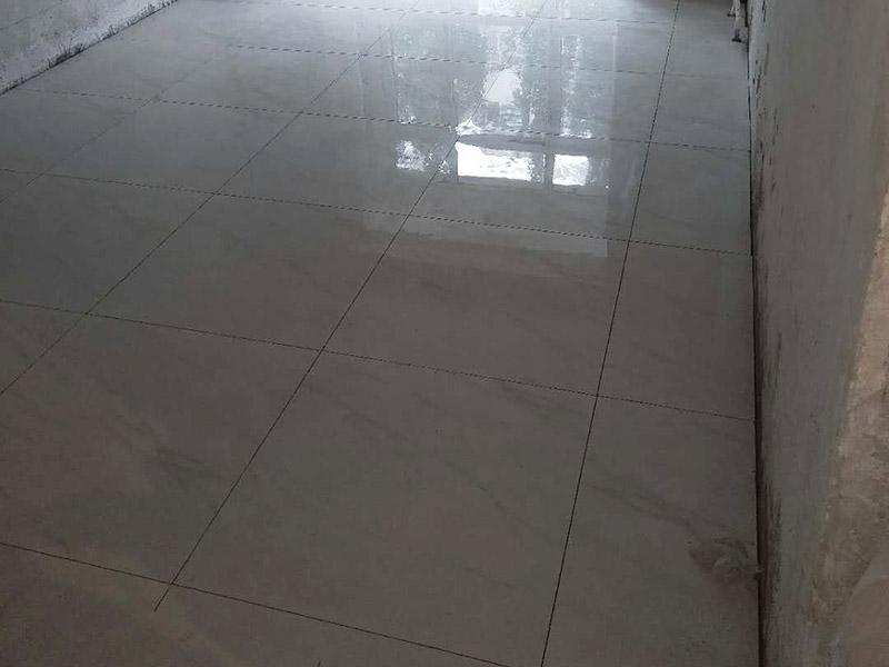 客厅地砖铺贴装修:首先将沙子和水泥按照3:1的比例混合后兑少量的水,使水泥和沙子混合到可以用手攥成团的黏稠度;接着在铺砖之前先将要铺的地方用水泼湿。将开始和好的水泥和沙子铲到你要铺瓷砖的地方,铲完以后用小铲子初步抹平。然后瓷砖背后抹上开始和好的那盆比较稠的水泥浆,再将抹好水泥的砖小心平放到要铺的地方,注意对缝。再用橡胶小榔头敲实,用水平尺找平。最后在侧边用小榔头的把手堵严实,完工。