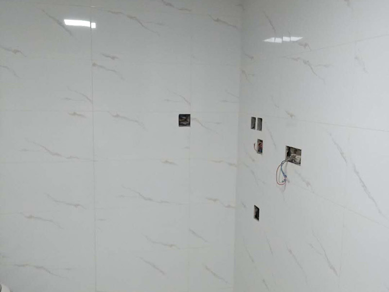 卫生间瓷砖铺贴:基层处理:把沾在基层上的浮浆、落地灰等用暂子或钢丝刷清理掉,再用扫帚将浮土清扫干净。找标高:根据水平标准线和设计厚度,在四周墙、柱上弹出面层的上平标高控制线。排砖:将房间依照砖的尺寸留缝大小,排出砖的放置位置,并在基层地面弹出十字控制线和分格线。铺设结合层砂浆:铺设前应将基底湿润,并在基底上刷一道素水泥浆或界面结合剂,随刷随铺设搅拌均匀的干硬性水泥砂浆。铺砖时应先在房间中间按照十字线铺设十字控制砖,之后按照十字控制砖向四周铺设,并随时用2m靠尺和水平尺检查平整度。大面积铺贴时应分段、分部位铺贴。养护:当砖面层铺贴完24h内应开始浇水养护,养护时间不得小于7d。