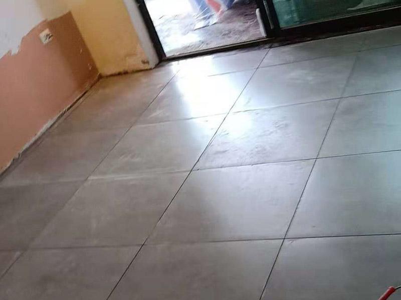 客厅地砖铺贴:铺贴的工具包括橡胶锤和粘结剂。在进行施工之前先把所需要的这些材料都整理好放在一旁备用;基层的处理工作对瓷砖的平整度有很大的影响,对于基层要做好清洁工作,还有找平工作。放样:在进行瓷砖的铺贴工作之前还事先找好垂直线,这样可以在铺贴的时候找到瓷砖的水平线,让瓷砖铺贴的更加的平整。粘结剂加水搅拌均匀,静置10分钟之后就可以使用。将瓷砖表面的浮灰清除,再在瓷砖背面均匀的涂抹上粘结剂,按照预铺的顺序将瓷砖铺贴在地面上,最后用橡胶锤轻轻拍打至服帖齐整。
