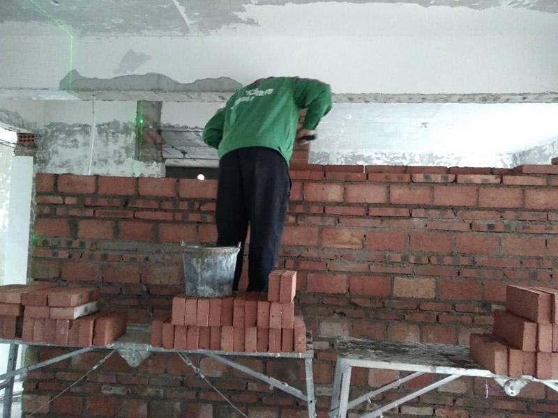 """砌墙装修:砌墙之前设计师会在现场进行砌墙""""放线"""",将需要砌墙的位置按施工图设计纸要求在地面、墙面弹好标线,做好放线,并用砖头摆放出砌墙位置。材料进场,要摆放整齐,方便拿取。卫生间和厨房是经常用水的地方,防水地梁可以有效的防止,在居住过程中卫生间地面的水,通过底部渗透到卧室或其它房间。 旧墙体因为水份已经凉干收缩好了,而新砌墙体也会有一个收缩过程,如果新旧墙体之间没有加固,时间长了墙体之间容易出现开裂,造成安全隐患,这时候就需要将新墙和旧之间用铁丝网加固 新砌墙体时门头必须做一道符合受力要求的水泥过梁。门头过梁可有效保证后期安装房门时,不会出现因受压而变形的情况。我们都知道在砌墙时每块红砖在放入灰浆上之后都要敲几下,以保证红砖与灰浆贴合,那么当顶部最后一排红砖再这样砌法,就无法完成这个动作,所以斜砌就能从侧面填灰浆再进行加固操作,这样就能保证墙体受力均匀保证质量。水泥墙浇水是件大事千万马虎不得,不浇水墙体的牢固性就不好,很容易产生隐患,所以墙体砌筑24小时后需要进行浇水养护,保证砂浆强度。"""