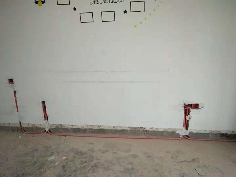 """局部改水电维修:确定改造方案——弹线开槽——布管固定线盒——穿线/焊接——水电管加固——进行绝缘/打压测试——水电管槽回填——水电节点验收。 水电布局到底是点对点,还是横平竖直,得根据现场情况定。一般来说,线路比较少的时候,可以点对点;但线路多时,强行点对点会让地面开满了槽,如同蜘蛛网一般,进而导致地面强度下降。高老庄的工做地面水电改造时,会尽可能让电线点对点,节约业主的钱;水路横平竖直,则是因为一般水路的连接件都是直角连接,很少有斜角。在布置水电线路时,有个原则叫""""水走天,电走地,厨卫走顶不走地,电在上,水在下""""。墙面尽量竖直开槽。承重墙禁止开斜槽、横槽,轻体墙也尽量不要开横槽,就算必需开,也不能超过30cm。在混凝土墙面上开槽时,不能锯断钢筋,同样需要凿浅槽并装好护套软管。 一般情况下,一根管道里可以穿两三根电线。如果再多,就要多加几根管道。电线不能都挤在一根管里,还是要留出一些空间,让人能比较顺畅地拽得动。这样将来如有需要,就可以直接拽着电线以旧换新,不需要重新再开一遍槽了。"""