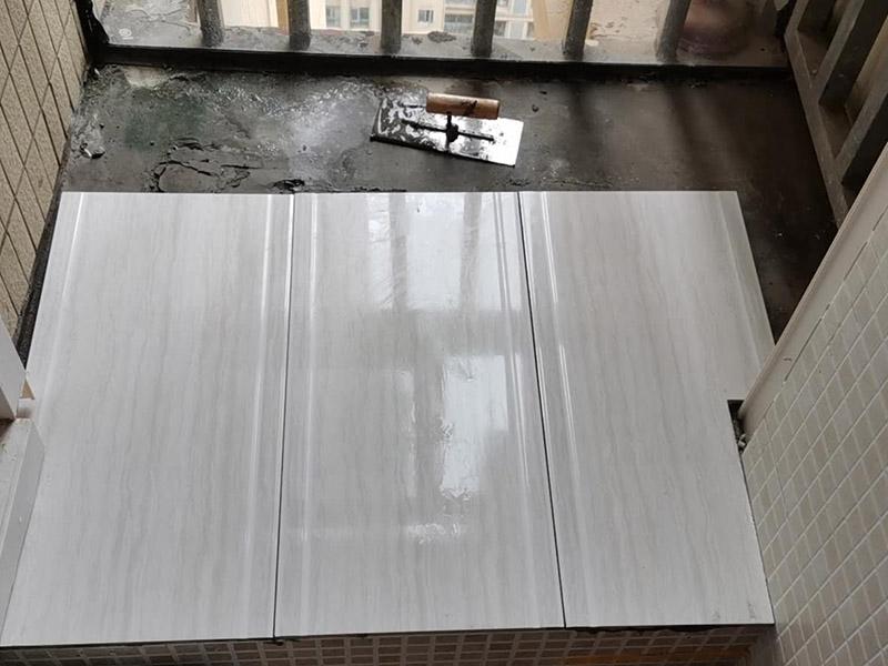 阳台瓷砖铺贴:准备粘结剂前,瓷砖不应浸水,但要用钢丝刷除去砖背面的松散物质,并用湿布抹去砖背的浮尘。然后按照生产商建议的比例将水或乳液放到搅拌桶中搅拌直至粘结剂均匀无结块。初始搅拌后的粘结剂应静置在搅拌桶中,直到生产商推荐的熟化时间过后搅拌一下再使用。 在铺压瓷砖前,在瓷砖背面也批一薄层粘结剂。这种双批法虽然用的材料和工时比较多,但却能够保证粘贴的质量和耐久性。 在粘结剂量置晾时间内,将准备好的瓷砖铺压到位,垂直于梳理方向轻微搓动以排出砖下的空气。铺贴到位后用橡皮锤轻击,用尺寸合适的十字定位架来调整表面平整度及接缝的平直。