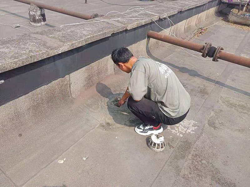"""屋面排水口维修:涂膜防水层依附于基层,基层质量好坏,直接影响防水涂膜的质量。因而在涂膜施工前,应对基层进行认真的检查和必要的处理,使之达到涂膜施工的要求。涂料的涂布应采取""""先高后低、先远后近、先立面后平面""""的施工顺序。同一屋面上先涂布排水比较集中的水落口、天沟、檐口等节点部位,再进行大面积的涂布。用滚刷或毛刷均匀地涂刷多遍,直到达到规定的涂膜厚度要求,不得漏底,待涂层干固后,才能进行下一道工序。当多遍涂布时,每遍涂刷方向应与上一遍方向相垂直。"""